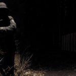 Mann mit dunkler Kapuzenmantel lehnt im Dunkeln an einer Metallstange.