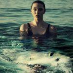 Eine Frau im Wasser schaut ängstlich auf den Hai, der vor ihr auftaucht.