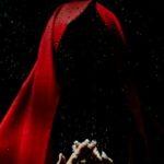 Eine Gestalt in rotem Kapuzenmantel.