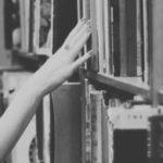 Eine Hand streicht über ein Bücherregal.
