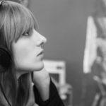 Eine junge Frau mit Kopfhörern sieht sich ein CD-Regal an.