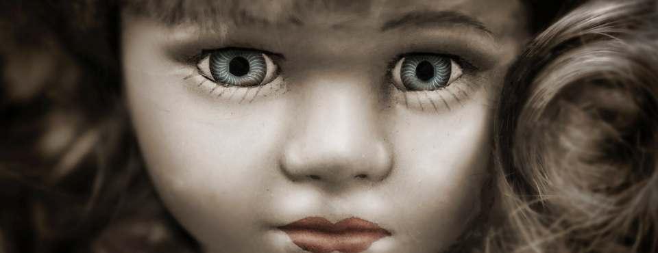 Ein blasses Puppengesicht mit starren blauen Augen.