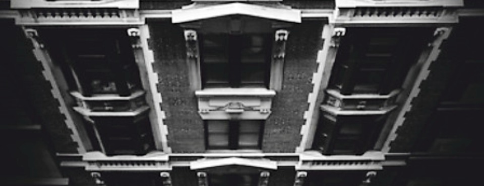 Graue Häuserwand eines noblen Hochhauses.