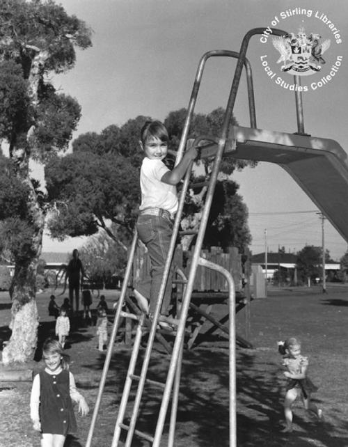 Eine Gruppe von Kindern spielt an einer Rutsche während im Hintergrund eine dunkle Gestalt mit Tentakeln hinter einem Baum lauert.